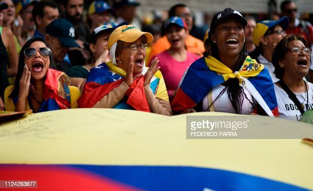 TOPSHOT Supporters of Venezuelan opposition leader and self declared acting president Juan Guaido cheer as they start gathering for a rally to press...