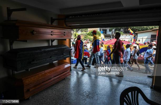 Supporters of Venezuelan opposition leader and self declared acting president Juan Guaido walks past a shop selling coffins as they take part in a...