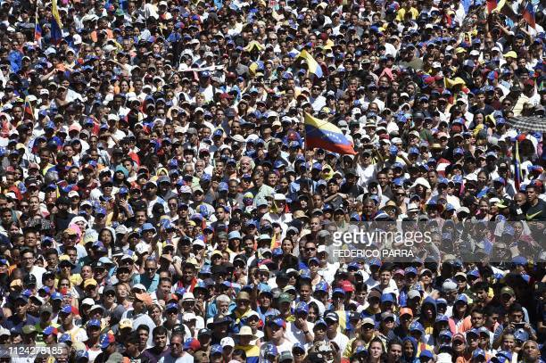 TOPSHOT Supporters of Venezuelan opposition leader and self declared acting president Juan Guaido take part in a rally to press the military to let...
