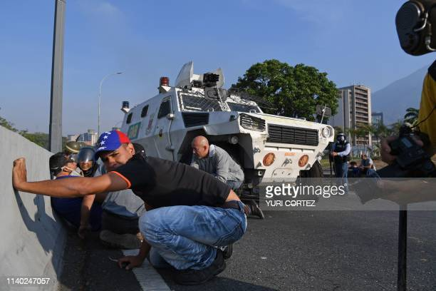 Supporters of Venezuelan opposition leader Juan Guaido take cover during clashes with security forces in Caracas on April 30 2019 Venezuelan...