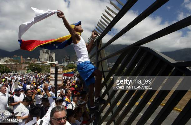 TOPSHOT Supporters of Venezuelan opposition leader Juan Guaido take part in a march in Caracas on February 23 2019 Venezuelan security forces fired...