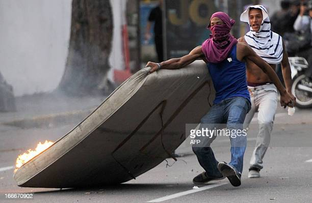 Supporters of Venezuelan opposition presidential candidate Henrique Capriles burn a mattress during a protest in Caracas on April 15 2013 Venezuela's...