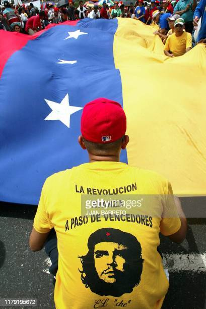 Supporters of Venezuelan President Hugo Chavez carry a giant flag during a march in Caracas 29 July 2002 Thousands of Chavez supporters demonstrated...