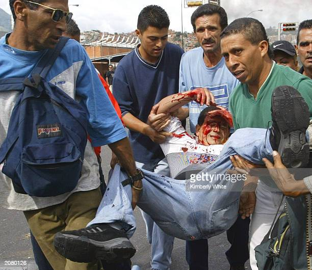 Supporters of Venezuelan President Hugo Chavez carry an injured man June 13 2003 in Caracas Venezuela Police reported that at least 11 people were...