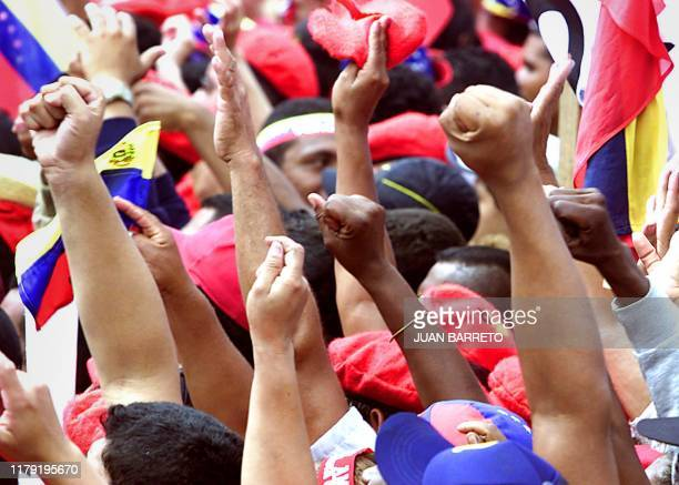 Supporters of Venezuelan President Hugo Chavez shout slogans during a march in Caracas 29 July 2002 Thousands of Chavez supporters demonstrated in...
