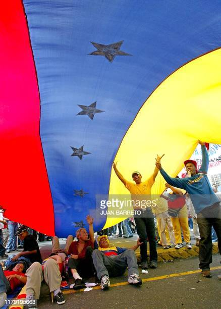 Supporters of Venezuelan President Hugo Chavez sit under a giant flag during a march in Caracas 29 July 2002 Thousands of Chavez supporters...