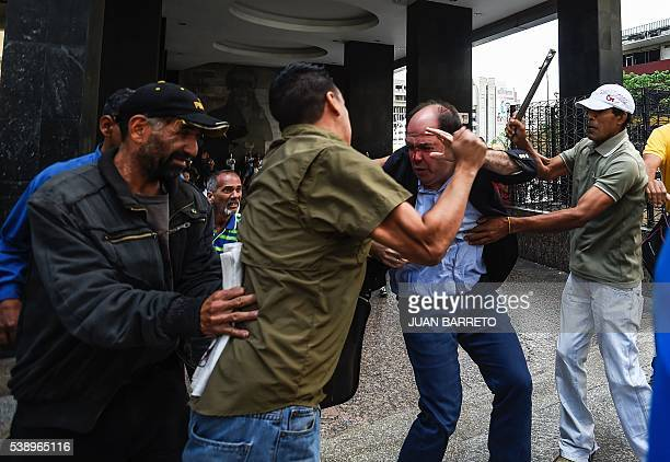 TOPSHOT Supporters of Venezuelan president Nicolas Maduro hit opposition deputy Julio Borges during a demonstration in front of the National...