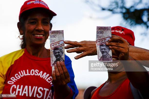 Supporters of Venezuelan President Nicolas Maduro hold 100Bolivar notes with the face of the president of the National Assembly oppositionist Henry...