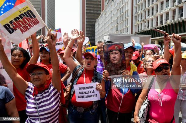 Supporters of Venezuelan President Nicolas Maduro take part in a rally with a portrait of late Venezuelan President Hugo Chavez in Caracas on May 22...