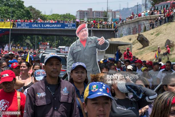 Supporters of Venezuelan President Nicolás Maduro hold a cardboard cutout of late Venezuelan President Hugo Chavez during a demonstration on May 1...