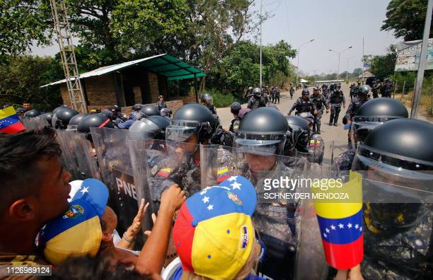 Supporters of Venezuela's opposition leader Juan Guaido demonstrate in front of members of Venezuela's Bolivarian National Police standing guard at...