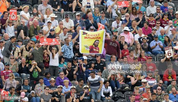 Supporters of West Indies' Chris Gayle cheer another six hit as he bats during the 2019 Cricket World Cup group stage match between West Indies and...