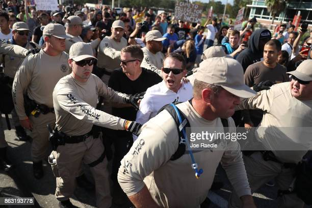 Supporters of white nationalist Richard Spencer who popularized the term 'altright' are escorted by Florida Highway Patrol officers through a crowd...