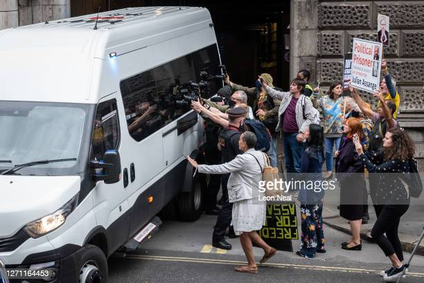 Supporters of Wikileaks founder Julian Assange and members of the media gather at the exit to the Old Bailey as a van believed to be carrying Assange...