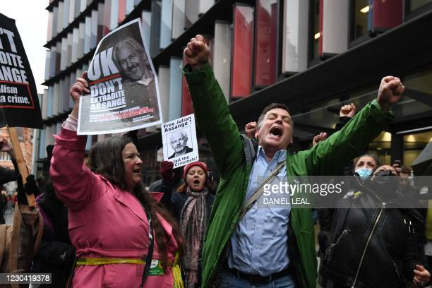 Supporters of Wikileaks founder Julian Assange celebrate outside the Old Bailey court in central London after a judge ruled that Assange should not...