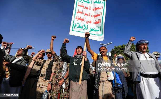 Supporters of Yemen's Huthi rebels chant slogans as they march with banners during a rally denouncing the United States and the outgoing Trump...