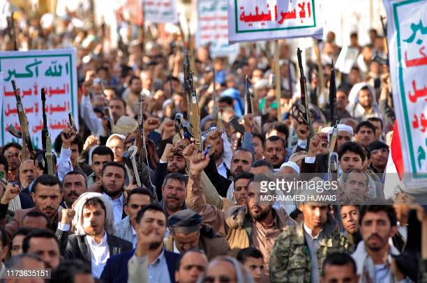 TOPSHOT Supporters of Yemen's Shiite Huthi rebels chant slogans and raise Kalashnikov assault rifles and signs showing the group's flag reading in...