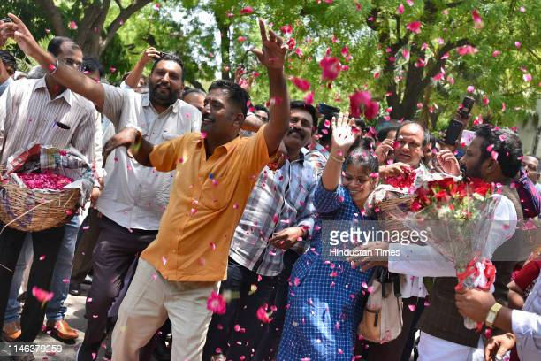 Supporters of YSR Congress Party chief Jaganmohan Reddy dancing as they wait for his arrival at the Andhra Bhawan on May 26 2019 in New Delhi India...