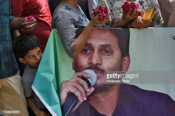 Supporters of YSR Congress Party chief Jaganmohan Reddy hold flower petals as they wait for his arrival at the Andhra Bhawan on May 26 2019 in New...