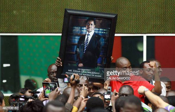 Supporters of Zambian Patriotic Front presidential candidate Edgar Lungu hold up his portrait at the Elections Results Centre after he was declared...