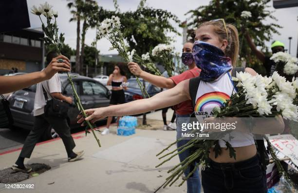 Supporters pass out flowers to protesters along Hollywood Boulevard during a peaceful demonstration over George Floyd's death on June 2, 2020 in Los...