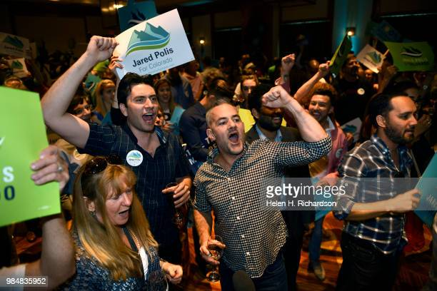 Supporters Paul Foley second from left and Rob Ryan right cheer for Democratic candidate Jared Polis as he accepts the nomination for Colorado...