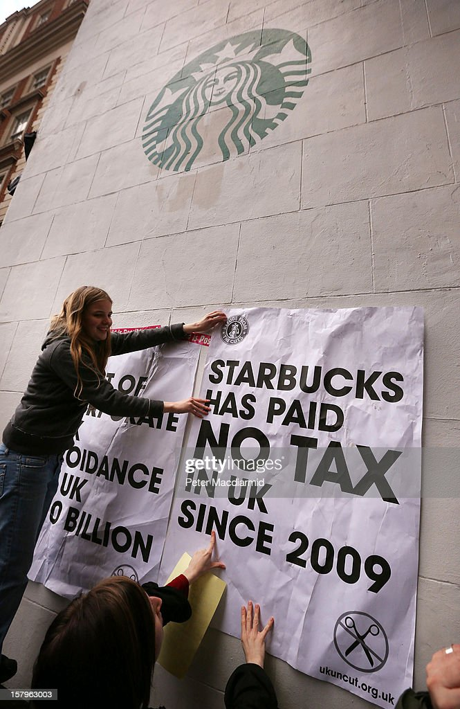 UK UNCUT supporters place posters on a sidewall of a Starbucks coffee shop near Regent Street on December 8, 2012 in London, England. UK UNCUT are holding a day of protests at various Starbucks throughout the United Kingdom after the coffe chain were revealed to be paying almost no corporation tax.