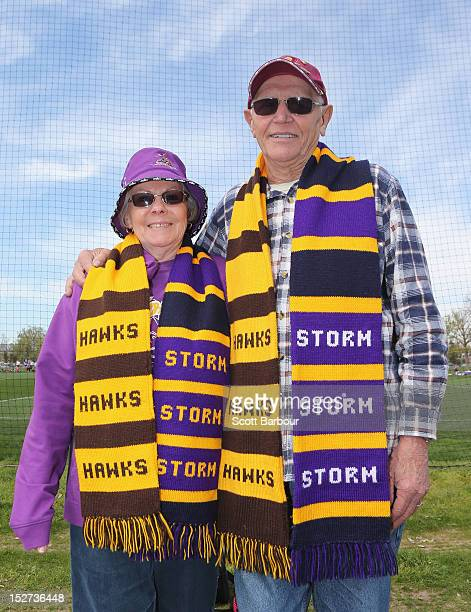 Supporters pose for a photo wearing their Melbourne Storm NRL and Hawthorn Hawks AFL scarves at a Melbourne Storm NRL training session at AAMI Park...