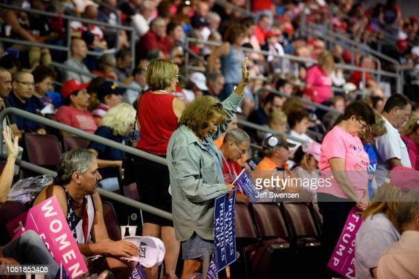 Supporters pray before a speech by US President Donald Trump at a rally at the Erie Insurance Arena on October 10 2018 in Erie Pennsylvania This was...