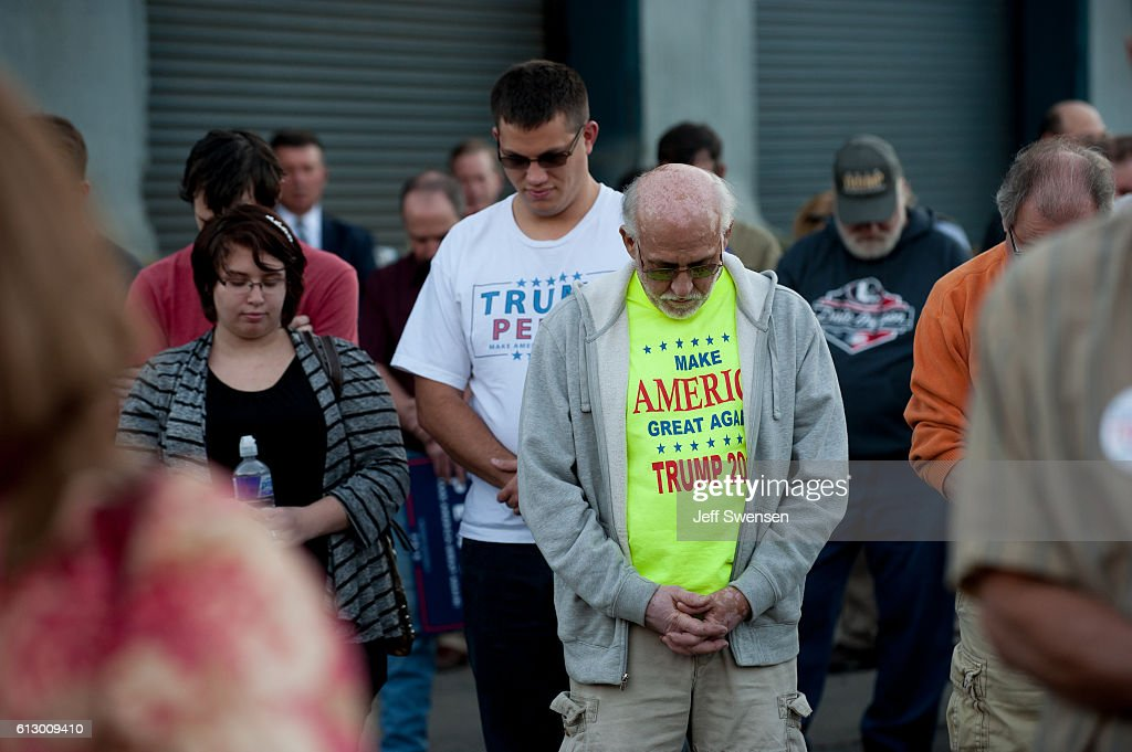 Supporters pray before listening to Republican candidate for Vice President Mike Pence after her spoke to close to 250 supporters at a rally at JWF Industries in Johnstown, Pennsylvania on October 6, 2016. Johnstown, Pennsylvania, with a population of 25,000 has been a traditionally democratic stronghold shifting to republican with a shrinking tax base and lost jobs, beginning in the 1970s, when 13,000 people lost their jobs at Bethlehem Steel, which now the location of JWF Industries.