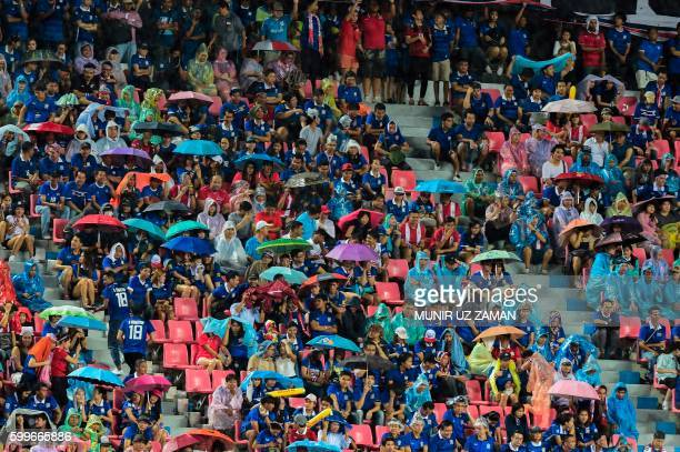 Supporters protect themselves from the rain as they attend the 2018 World Cup football qualifying match between Thailand and Japan in Bangkok on...
