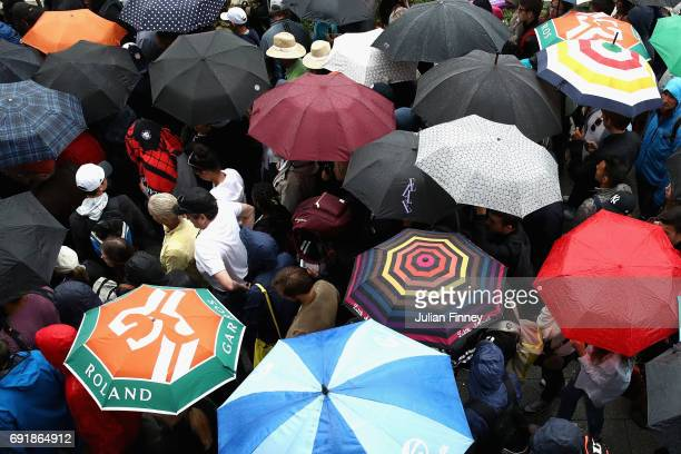 Supporters put up their umbrellas to take cover from the rain on day seven of the 2017 French Open at Roland Garros on June 3 2017 in Paris France