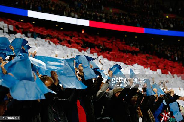 Supporters raise blue white and red papers to form French national flag wave the national flags prior to the International Friendly match between...
