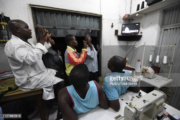 Supporters raise fingers and watch television as they celebrate in a shop the reelection of the candidate of the ruling All Progressives Congress...
