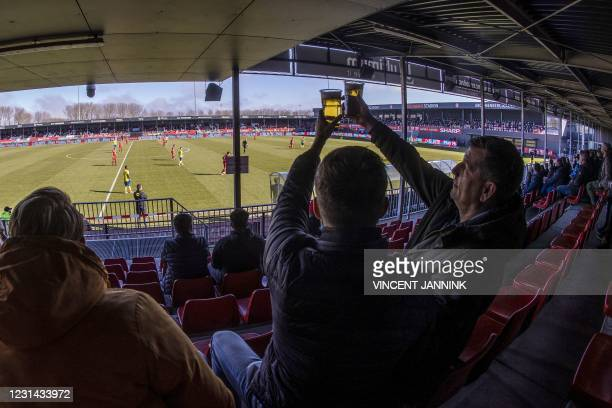 Supporters raise their beer glasses as they sit in a stand during a football match between Almere City FC and Cambuur in Almere, The Netherlands on...