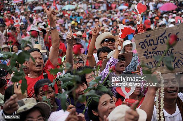 Supporters raise their fingers and shout slogans during an election rally by candidate for the opposition Puea Thai party Yingluck Shinawatra the...