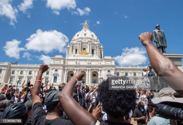 Supporters raise their fists while standing at the State Capitol during a National Mother's March in St. Paul, Minnesota July 12, 2020. - Mothers,...