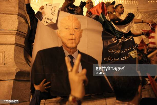 Supporters raise up the victory sign next to a giant poster of Kais Saied set up in the street during the celebration of Kais Saied Victory in...