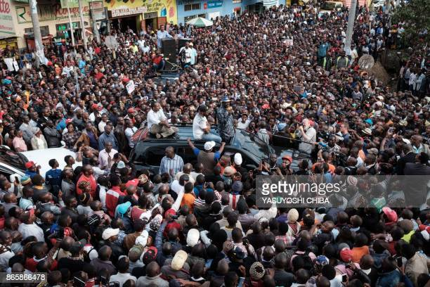 Supporters react as Kenya's opposition leader Raila Odinga of the opposition National Super Alliance coalition, flanked by Mombasa Governor Hassan...