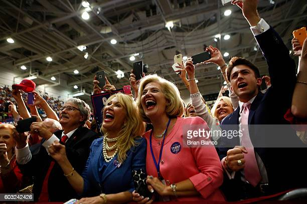 Supporters react as Republican presidential candidate Donald Trump takes to the stage at a rally on September 12 2016 at US Cellular Center in...