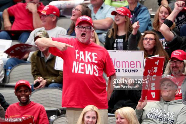 Supporters react as US President Donald Trump speaks during a Keep America Great Campaign Rally at American Airlines Center on October 17 2019 in...
