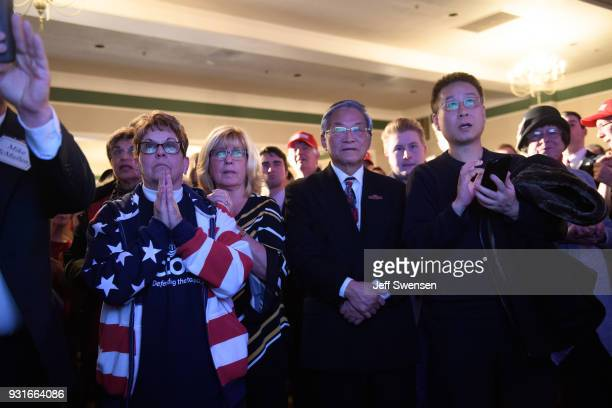 Supporters respond to early election results at an Election Night event for GOP PA Congressional Candidate Rick Saccone as the polls close on March...