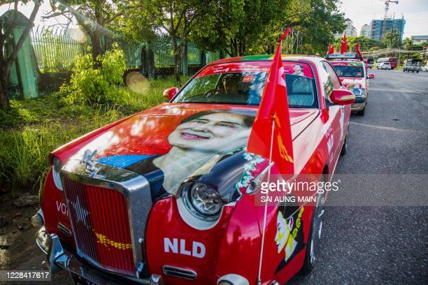 Supporters ride vehicles decorated with the National League for Democracy party flag and portrait of Myanmar's de-facto leader Aung San Suu Kyi,...