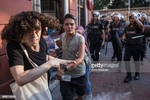 LGBT supporters run as police fire tear gas on July 1 2018 in Istanbul Turkey For the fourth year the 2018 LGBT Pride March was banned by authorities...