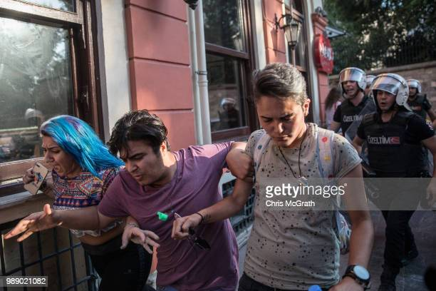 LGBT supporters run from police on July 1 2018 in Istanbul Turkey For the fourth year the 2018 LGBT Pride March was banned by authorities organizers...