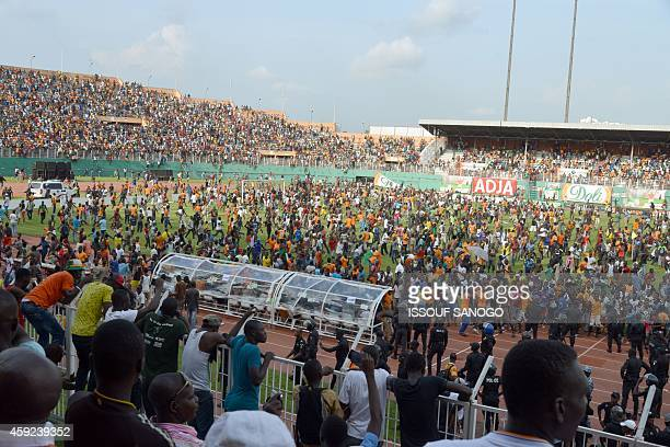 Supporters run on the pitch at the Felix HouphouetBoigny Stadium in Abidjan on November 19 2014 at the end of the 2015 Africa Cup of Nations group D...