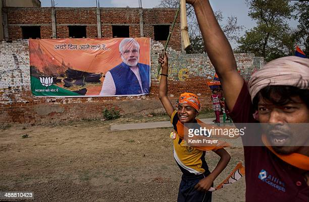 Supporters run passed a banner showing BJP leader Narendra Modi at a rally by the leader on May 8 2014 in Rohaniya near Varanasi India Thousands of...