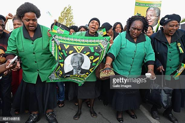 Supporters sing and dance to celebrate the life of Nelson Mandela outside his former home in Vilakazi Street, Soweto Township, on December 7, 2013 in...