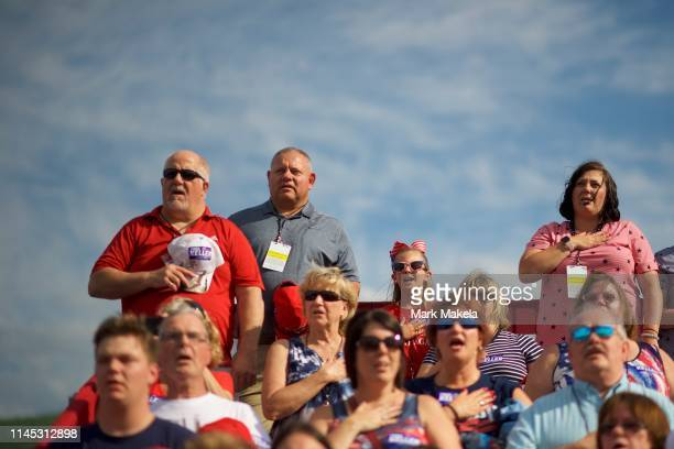 Supporters sing the national anthem before the arrival of US President Donald J Trump at a MAGA rally at the Williamsport Regional Airport on May 20...