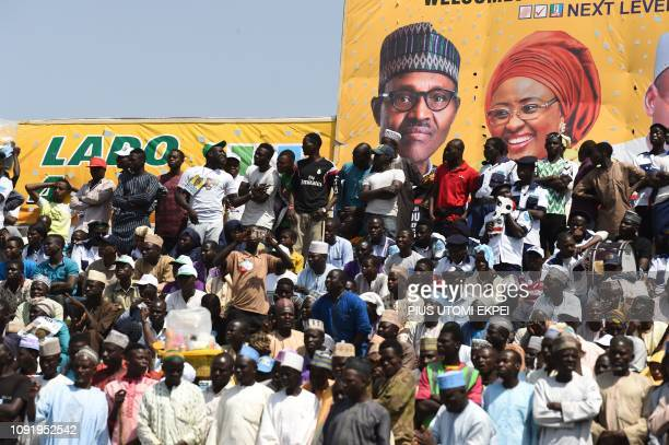 Supporters sit beside poster of candidate of the ruling All Progressives Congress candidate President Mohammadu Buhari and his wife Aisha during his...